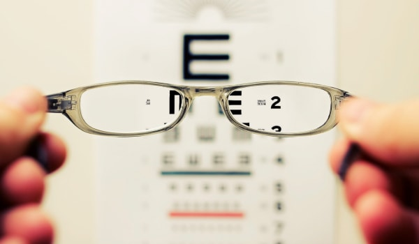 Holding glasses with eye chart in background