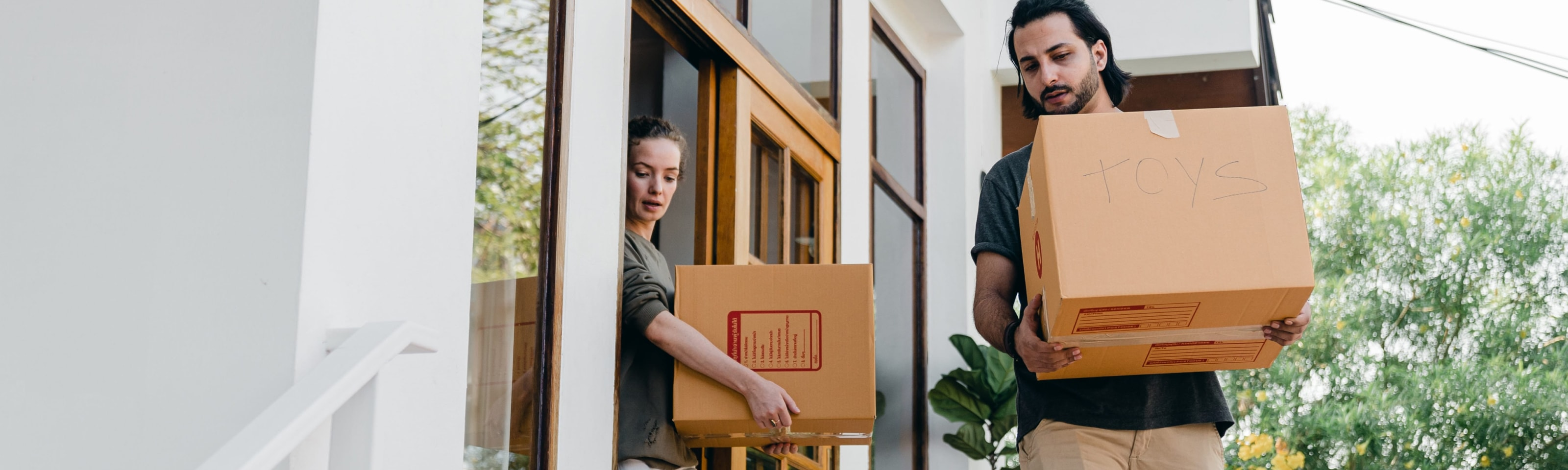 couple carrying boxes while moving out of home